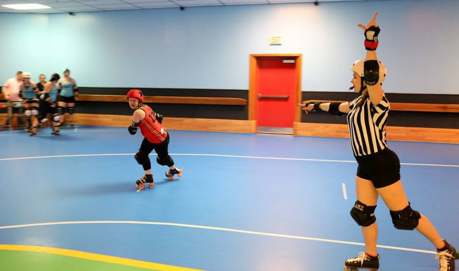 A roller derby skater strides, a ref points at her