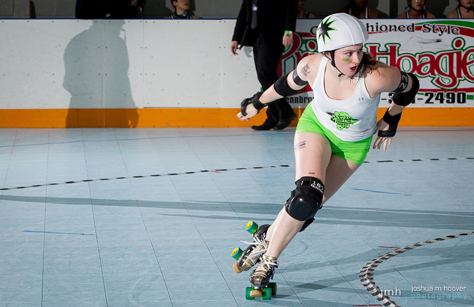A jammer skates around the roller derby track in green shorts