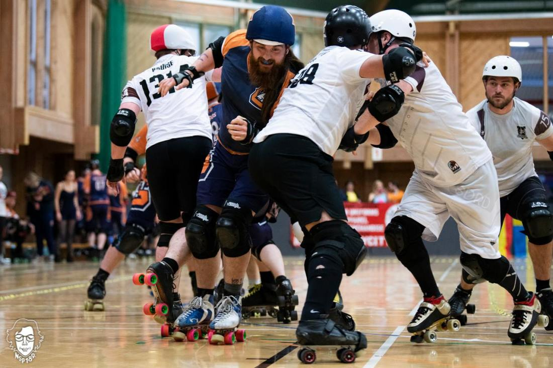 A jammer is breaking through a pack of roller derby skaters